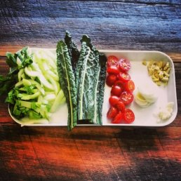 Chicken and kale soup ingredients: bok choy, kale, tomato, leek, ginger, garlic.